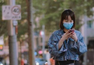 Woman in mask using smartphone